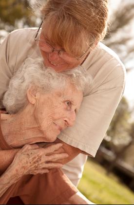 Abrazo entre cuidadora y anciana